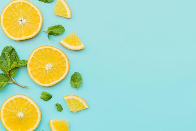 Rodajas de naranja y hojas de menta sobre fondo Foto gratis