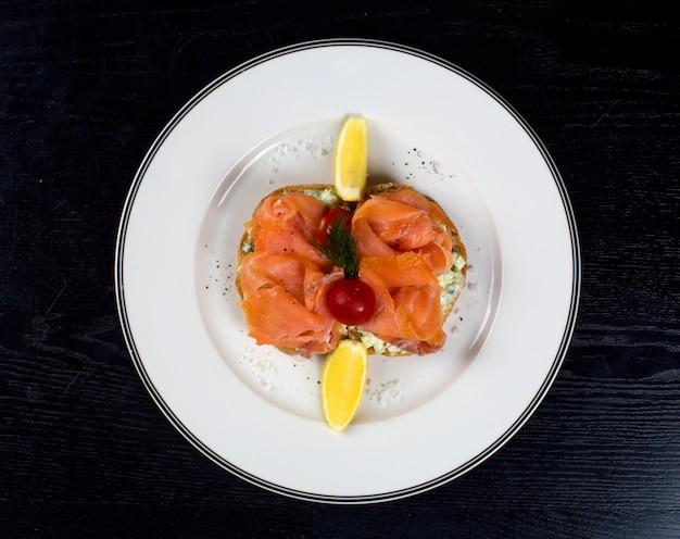 Rodajas de salmón ahumado con limones laterales Foto gratis