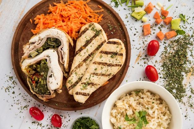 Rollito de pollo y pechuga en plato de madera arreglado con trozos de vegetales Foto gratis