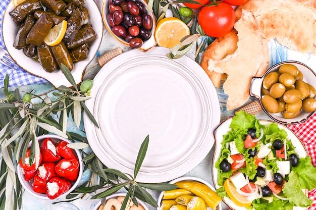 Rollitos de col turca y diversos aperitivos de la cocina nacional. arroz en hojas de uva y aceitunas. comida para un almuerzo tradicional oriental. espacio libre para texto, plato vacío Foto Premium