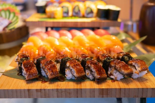 Rollo de salmón a la plancha en conjunto de sushi, concepto de fondo Foto Premium