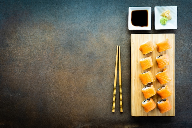 Rollo de sushi de salmón pescado carne maki en placa de madera Foto gratis