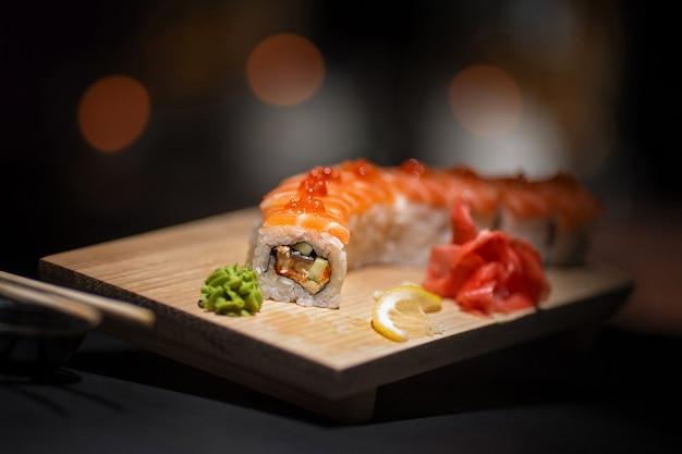 Rollos apetitosos se encuentran en una placa de madera. Foto Premium