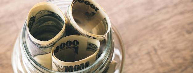 Rollos de billetes de dinero yen japonés en el tarro de cristal Foto Premium