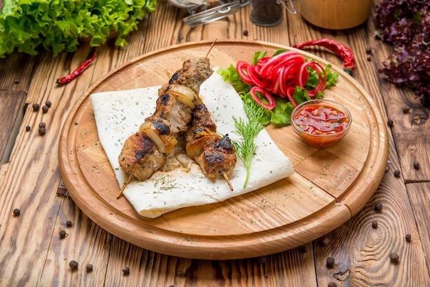 Rollos de carne a la parrilla con cebolla roja y zumaque en pita Foto Premium