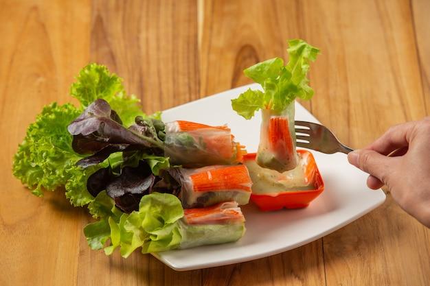 Rollos de ensalada tailandesa con salsa picante de ajo colocado en un piso de madera. Foto gratis
