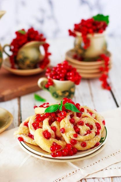 Rollos de galleta de requesón con grosellas rojas en plato de cerámica con té o café de cerámica vintage, hora del té, desayuno, dulces de verano Foto gratis