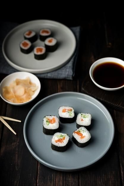 Rollos de sushi de alta vista en platos y papas fritas Foto gratis