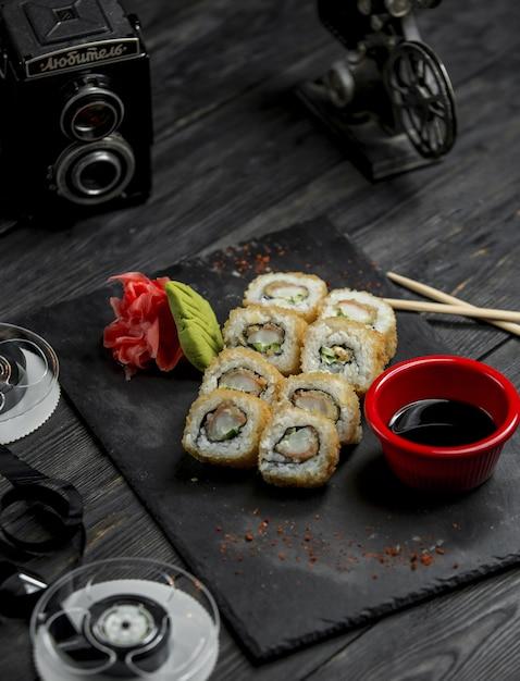 Rollos de sushi, california caliente con salsa y jengibre rojo en bandeja de piedra Foto gratis