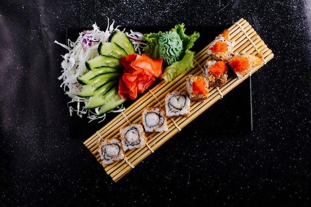 Rollos de sushi en una estera de sushi con wasabi, jengibre y pepino. Foto gratis
