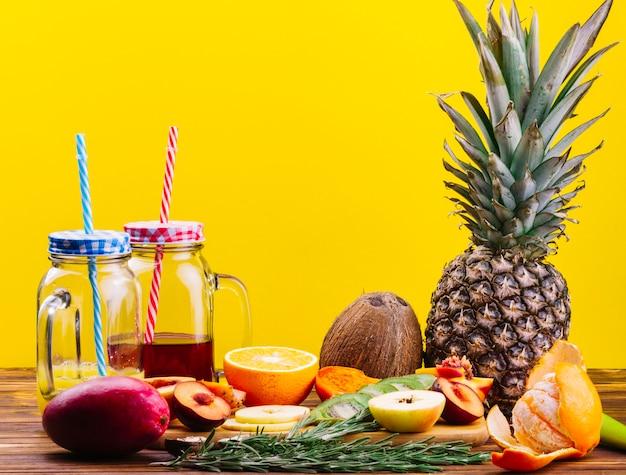 Romero; coco; frutas y jugo en taza de tarro de masón en mesa de madera sobre fondo amarillo Foto gratis