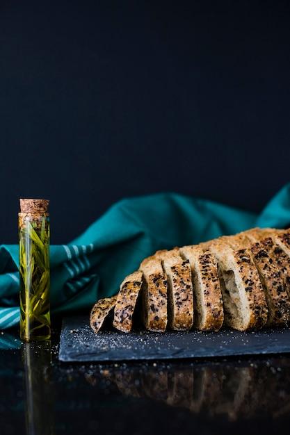 Romero en tubo de ensayo y rebanadas de pan integral en rebanadas de pan sobre fondo negro Foto gratis