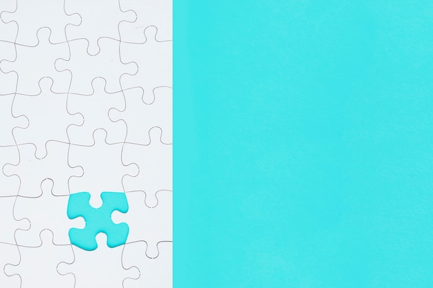 Rompecabezas blanco con la pieza que falta en el fondo turquesa Foto gratis