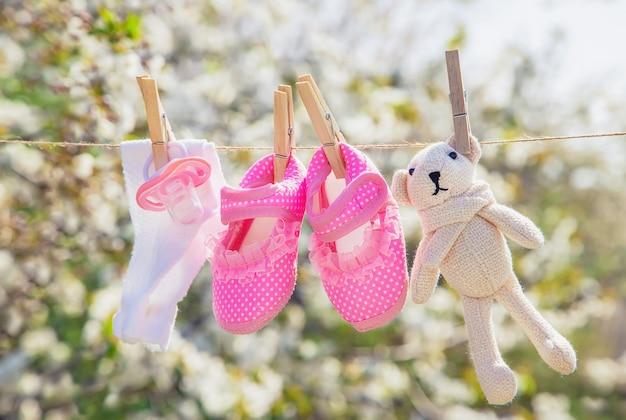 La ropa y los accesorios para bebés pesan en la cuerda después de lavarse al aire libre. enfoque selectivo Foto Premium