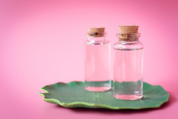 Rosa botella de jabón líquido en loto verde dejar sobre rosa Foto Premium