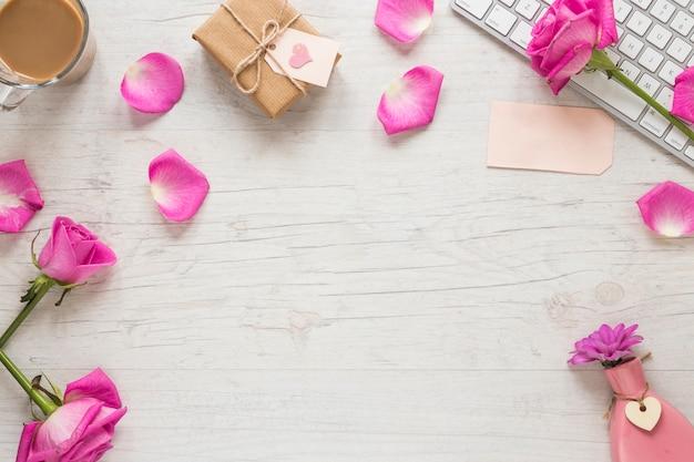 Rosa flores con caja de regalo y teclado en mesa Foto gratis