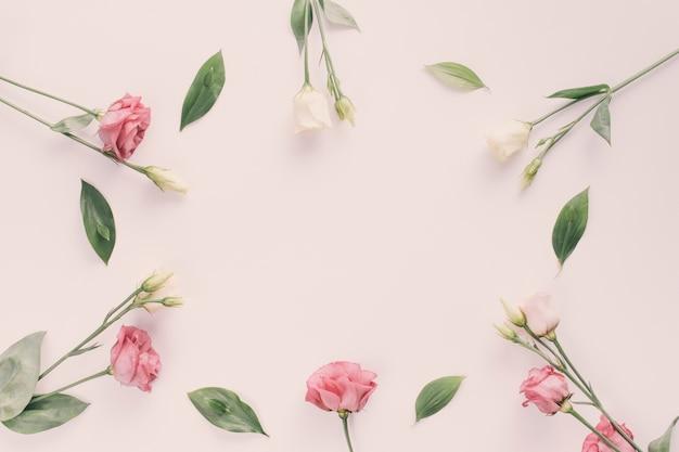 Rosa flores con hojas verdes en mesa Foto gratis