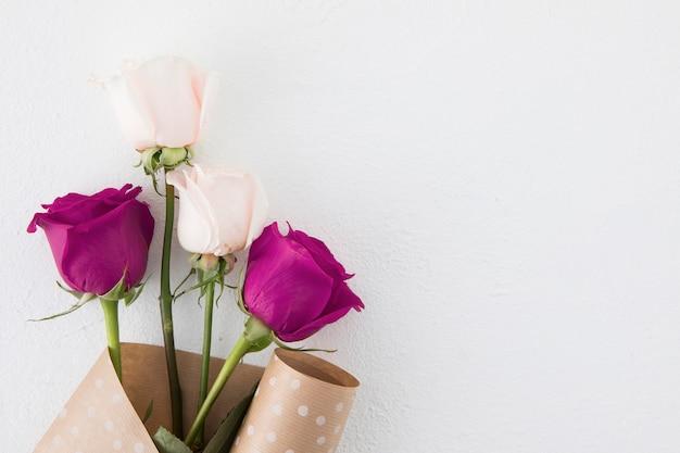 Rosa flores en paquete de papel en mesa blanca Foto gratis