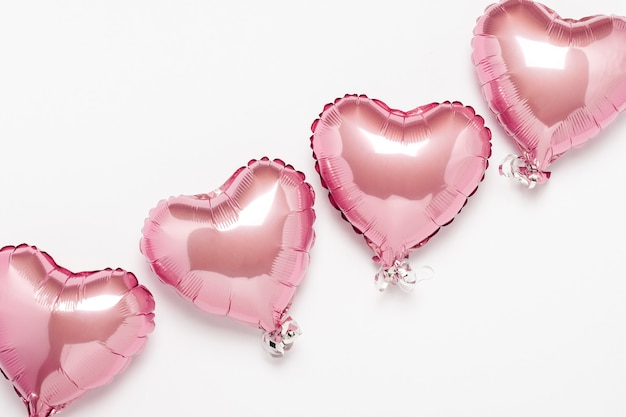 Rosa globos de aire en forma de corazón sobre una superficie blanca. concepto de boda, día de san valentín, zona de fotos, amantes. . vista plana, vista superior Foto Premium