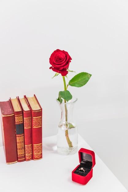 Rosa roja fresca en el florero cerca de la caja actual con anillo y libros en la mesa Foto gratis