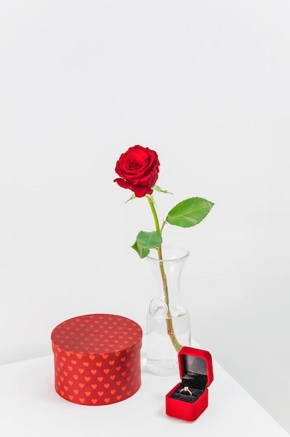 Rosa roja fresca en jarrón cerca del presente y caja de joyería con anillo en la mesa Foto gratis