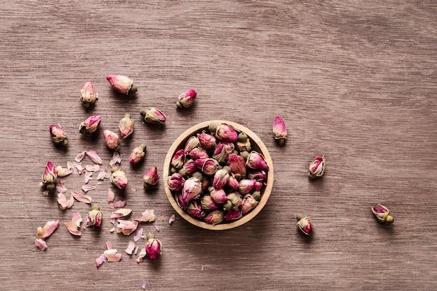 Rosa roja seca rosa brotes en tazón de madera con pétalos Foto Premium