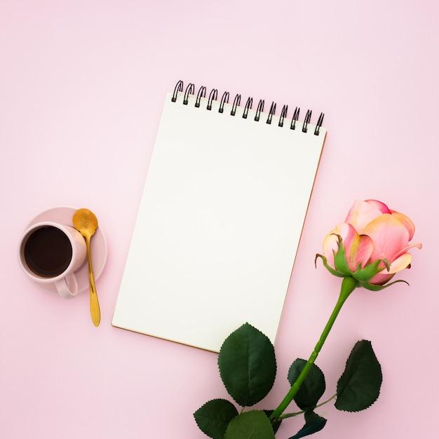 Rosa rosa, café y libreta Foto gratis