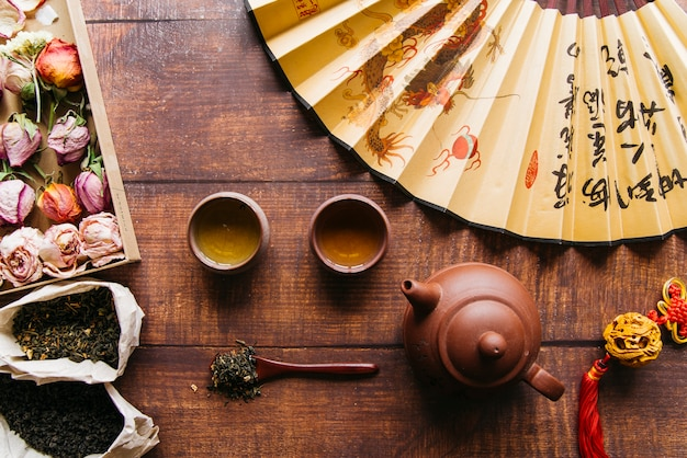 Rosa seca con hierba de té con tetera y tazas de té y abanico chino en mesa de madera Foto gratis