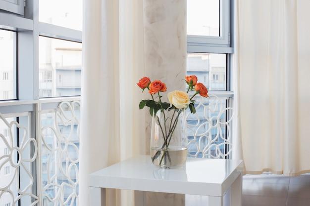 Rosas en florero sobre mesa blanca Foto Premium