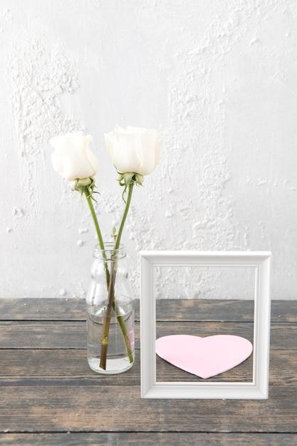 Rosas en jarrón con marco y corazón de papel. Foto gratis