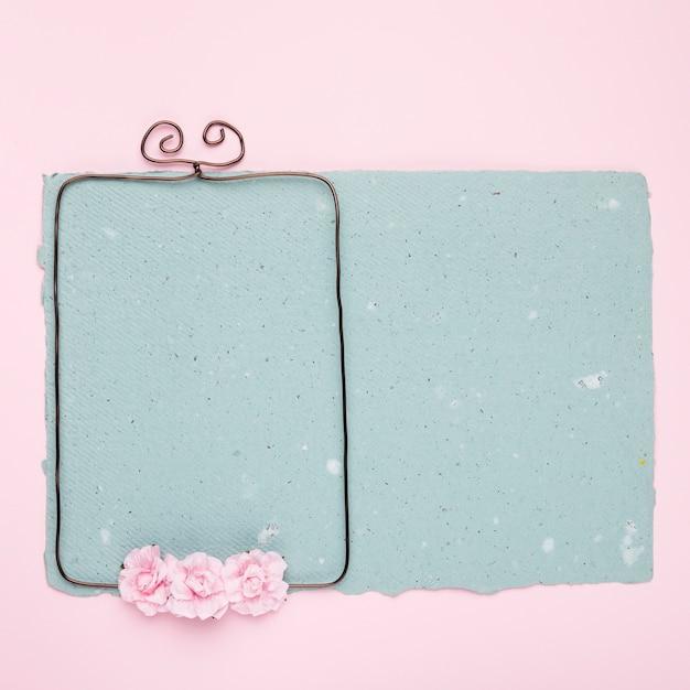 Rosas en marco con cable sobre el papel azul sobre fondo rosa Foto gratis