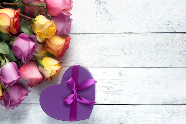 Rosas púrpuras y amarillas, cuadro presente sobre fondo blanco de madera Foto Premium