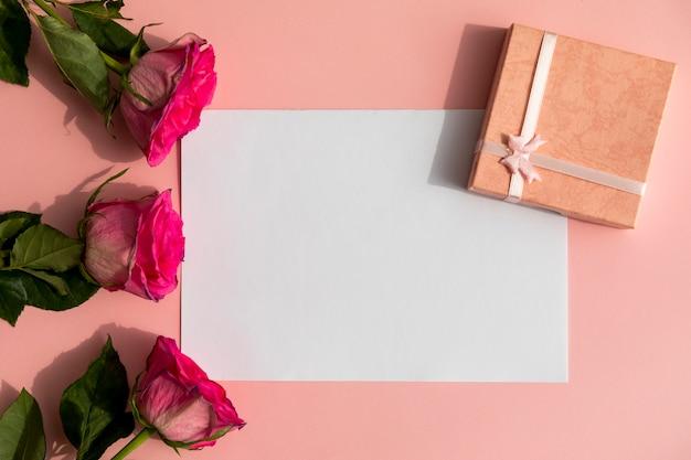 Rosas y regalo con espacio de maqueta. Foto gratis