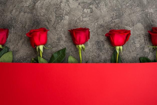 Rosas rojas y papel rojo Foto Premium
