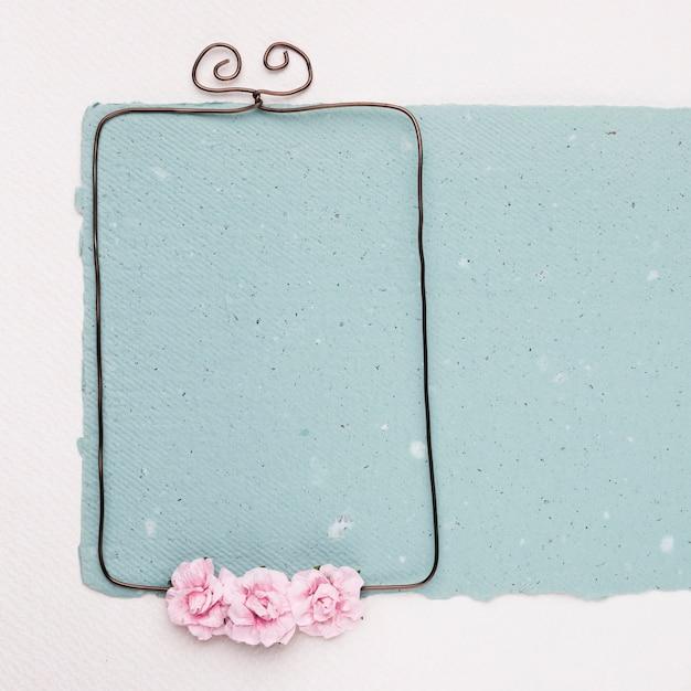 Rosas rosadas en marco metálico vacío sobre el papel azul sobre fondo blanco Foto gratis