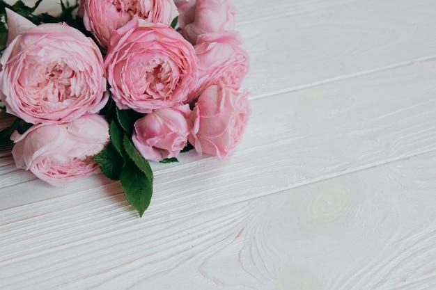 Rosas rosadas en una mesa blanca, concepto de verano Foto Premium
