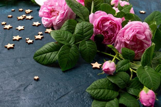 Rosas rosas y estrellas sobre una superficie azul oscuro. concepto de café Foto Premium