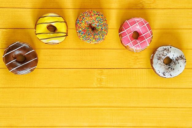 Rosquillas y confeti en una mesa de madera. Foto Premium