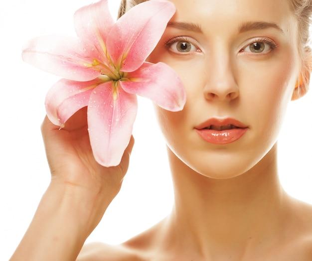 Rostro de belleza de la joven mujer con lirio rosa Foto Premium