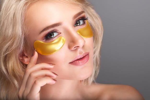 Rostro de belleza de mujer con máscara debajo de los ojos. Foto Premium
