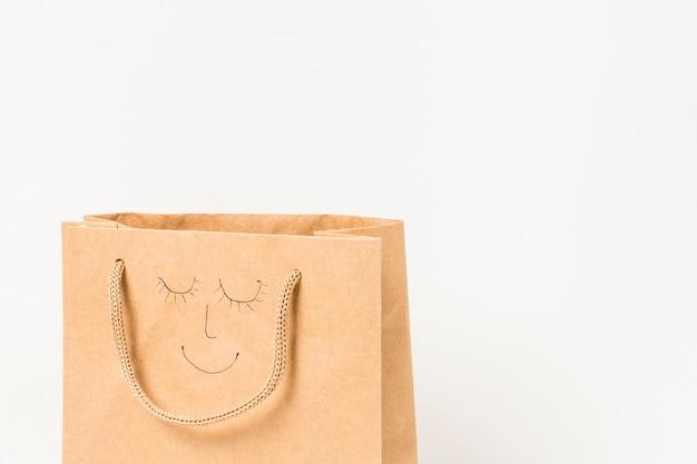 Rostro humano dibujado en una bolsa de papel marrón contra la superficie blanca Foto gratis