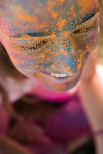 Rostro de mujer sonriente con polvo holi azul y amarillo Foto gratis