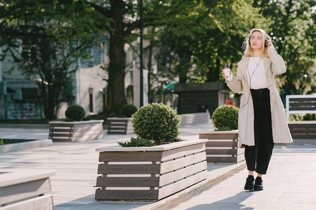 Rubia camina en la ciudad de verano con una taza de café Foto gratis