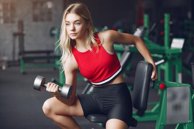 Rubia deportiva en un entrenamiento de ropa deportiva en un gimnasio Foto gratis