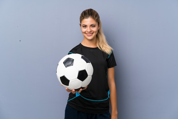 Rubia futbolista adolescente chica sobre pared gris Foto Premium