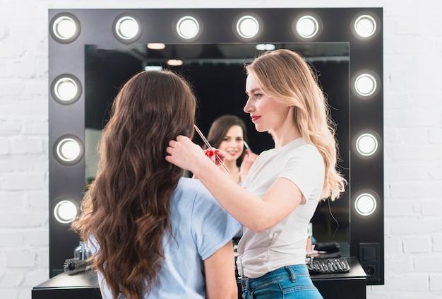 Rubia haciendo maquillaje de ojos para cliente con cepillo Foto gratis