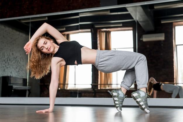 Rubia joven bailando delante del espejo Foto gratis