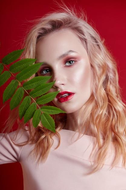 Rubia sexy con maquillaje rojo brillante. Foto Premium