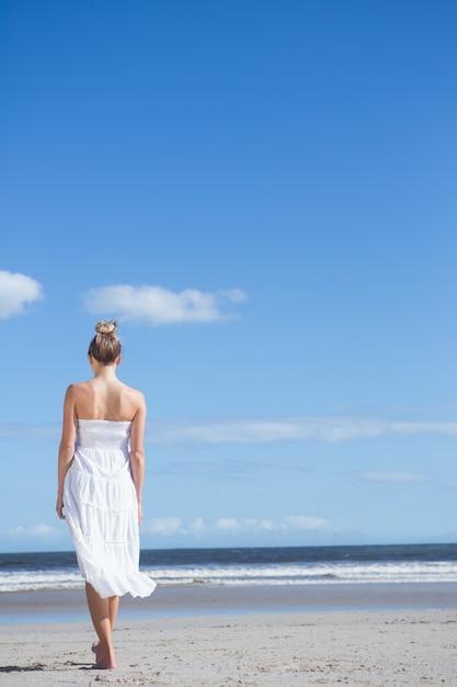 Rubia en vestido blanco caminando en la playa | Descargar