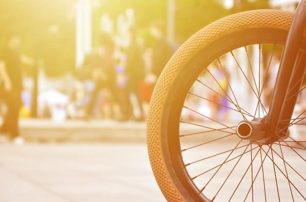 Una rueda de bicicleta bmx con el telón de fondo de una calle borrosa con ciclistas. Foto Premium